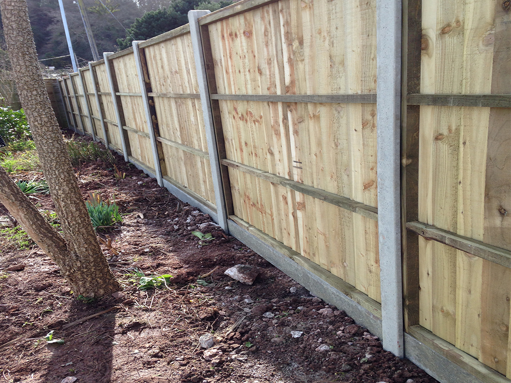 Close board fencing panels using concrete posts & gravel boards